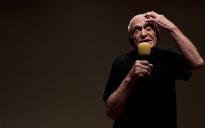A man speaks into a microphone and holds up his left hand to his head