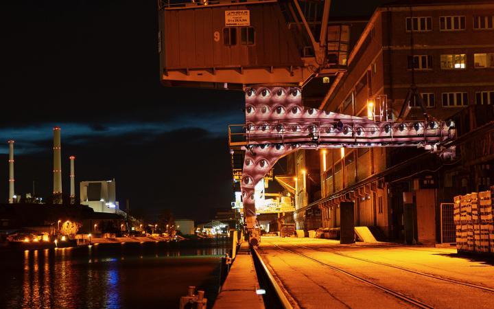 Ein Hafen bei Nacht. Auf einer Säule, die wie eine Torbogen gestaltet ist, sind viele Augenpaare projiziert. Die Augen blicken offen in verschiedene Richtungen.