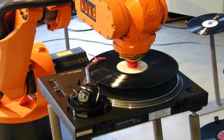 Ein orangener Roboterarm legt Schallplatten auf.
