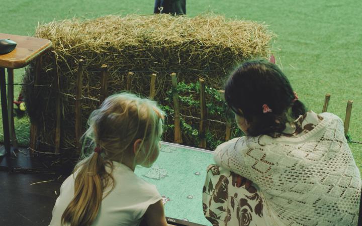 Zwei Kinder sitzen kniend vor einem Bildschirm