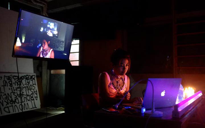 Eine Frau sitzt in einem dunklen Raum, sie wird von ihrem Laptop angestrahlt.