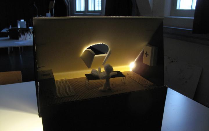 Wir sehen ein geheimnisvoll erleuchtete Miniatur-Bühnenkulisse, eine Schaumstofffigur liegt auf einem Krankenbett, davor steht eine zweite Figur.