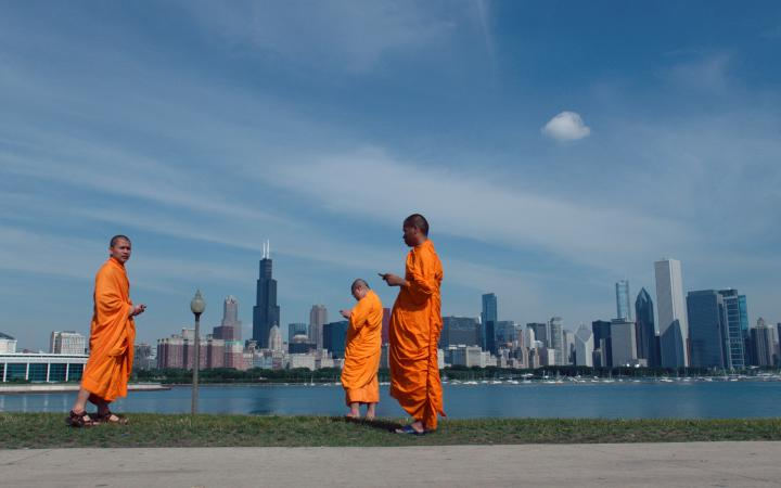 Three men in Tibetan costumes are standing in front of the submarine skyline of a large modern city. All three are looking at their smartphone.