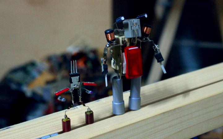 Auf einem Holzbalken stehen zwei aus Elektronikschrott zusammengelötete Roboter.