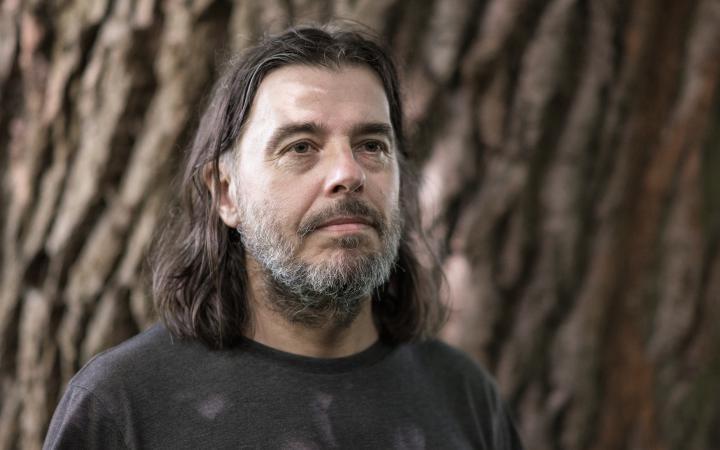 Zu sehen ist das Porträt eines bärtigen Mannes mittleren Alters mit langen Haaren. Er steht vor einem Baum und schaut an der Kamera vorbei.