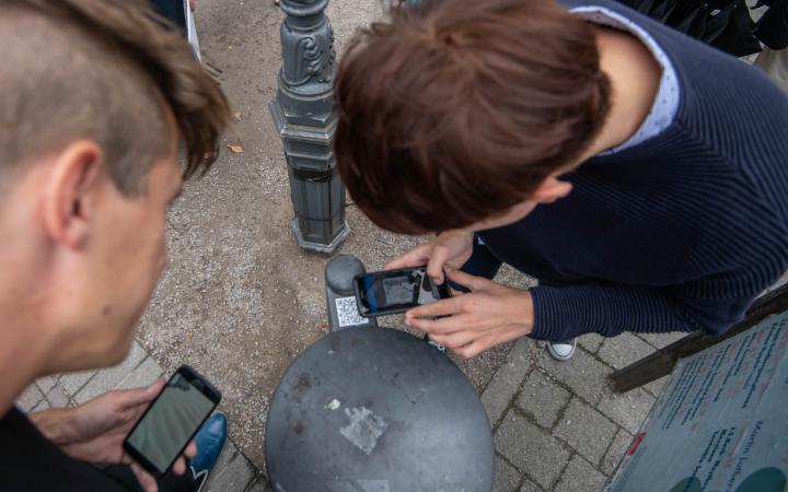 Foto von zwei Personen, die mit ihrem Smartphone einen QR-Code auf einem Mülleimer scannen.