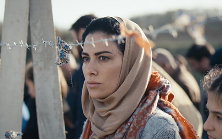 Eine Frau mit Kopftuch steht hinter einem Stacheldrahtzaun.