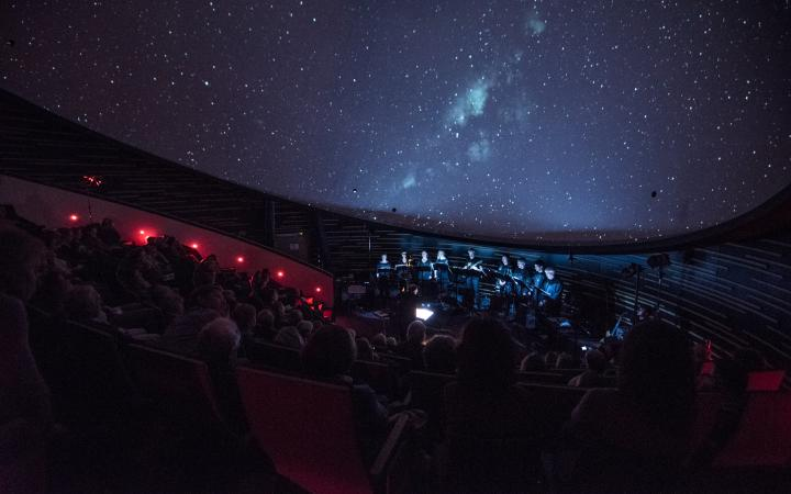 The KlangForum on stage in front of a projected starry sky