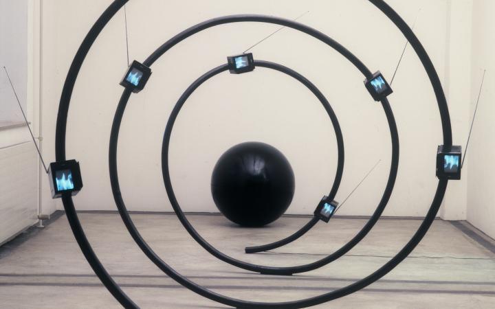 Eine Skulptur aus einer schwarzen Spirale mit kleinen Bildschirmen, die Arbeit heißt »The name« und stammt von Michael Bielicky.