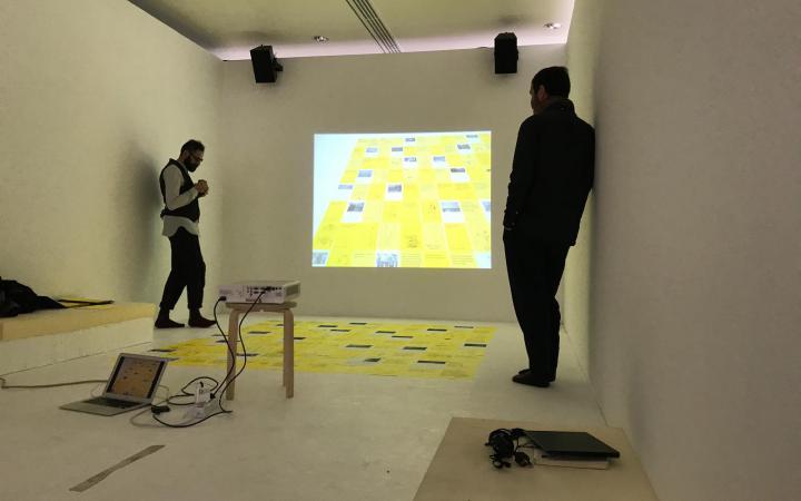 Zwei Personen stehen in einem Raum vor einem Beamer mit einem Laptop.