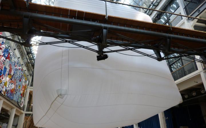 Ein sehr großer weißer Luftballon hängt in einem Lichthof