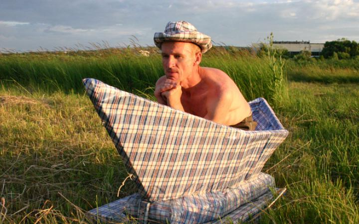 A man who is naked from the waste up sits in an oversized paper boat which stands on a green