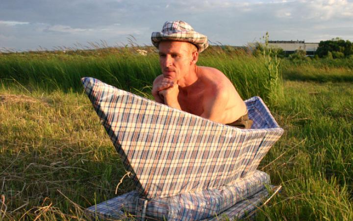 Ein Mann mit nacktem Oberkörper sitz in einem überdimensional großen Papierboot, das auf einer Wiese steht