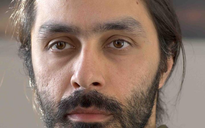 zu sehen ist das Porträt eines Mannes mit bart und langen haaren, welche zu einem Zopf gebunden sind.