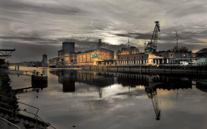 The photo shows illuminated industrial buildings along the Rhine. The sky is in gloomy evening mood.