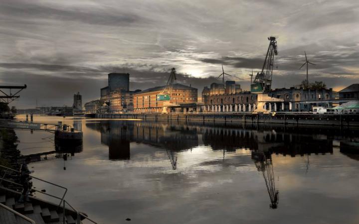 Das Foto zeigt beleuchtete Industriebauten entlang des Rheins. Der Himmel ist in gräulicher Abendstimmung.