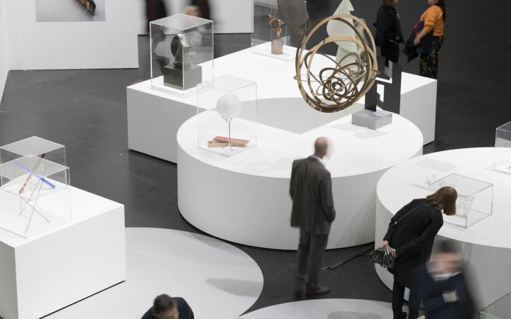 Sculptures stand on white pedestals, visitors are on their way in between.