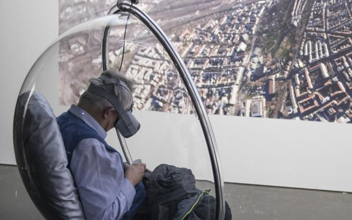 A visitor with VR glasses sits in a hanging semicircular armchair made of transparent plastic.