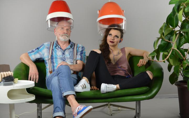 Two people sit on a green sofa, their heads are stuck under a hairdresser's hood.