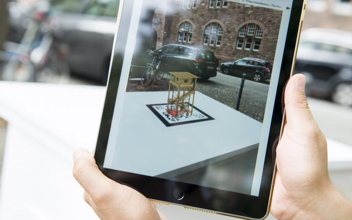 Two hands hold an iPad on which a 3D animated miniature monument can be seen over the QR code of the work »The Peoples Monuments«..