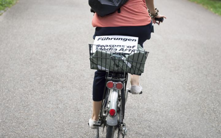 There's a white laminated sign in a bike basket that says »Guided Tours Seasons of Media Arts«.