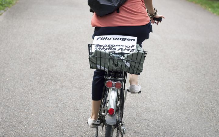 In einem Fahrradkorb liegt ein weißes, laminiertes Schild, darauf steht »Führungen Seasons of Media Arts«
