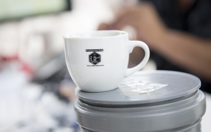 Zu sehen ist eine weiße Kaffetasse auf der das Transparenz Cafè Logo zu sehen ist.