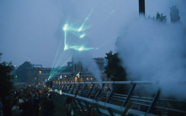 The picture shows a green laser show with audience