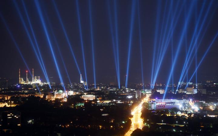 Die Stadt Karlsruhe auf einem Foto bei Nacht, am Himmel sind helle Strahlen zu sehen, die Gebäude der Stadt sind erleuchtet.