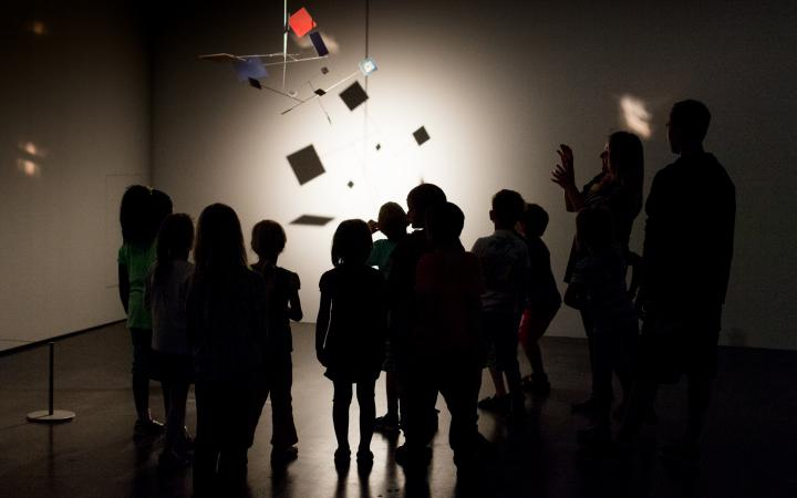Kids are standing in the dark museum, gazing at an mobile, that is illuminated