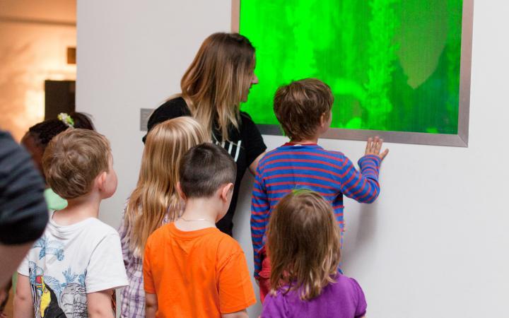 Eine Gruppe von Kindern betrachtet ein grün leuchtendes Bild.
