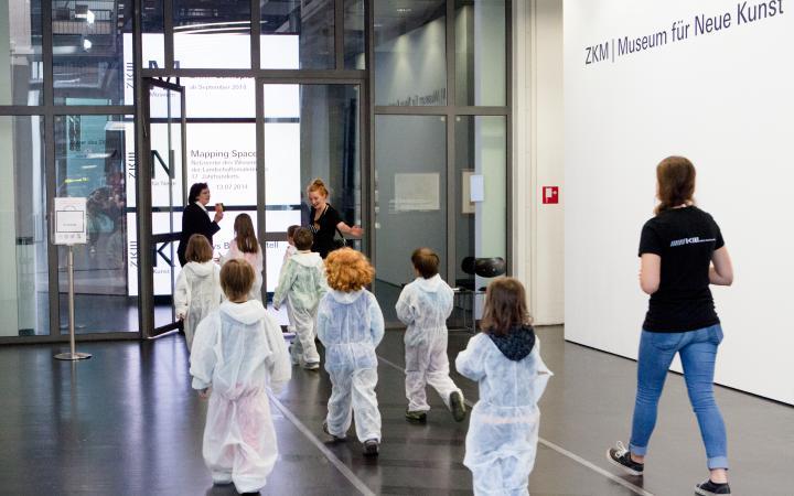 Kinder in weißen Overalls betreten das Museum für Neue Kunst