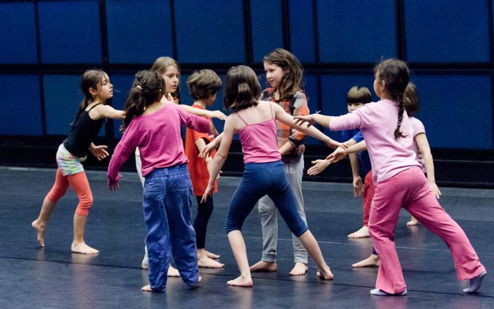 Eine Gruppe von Kindern bei einem Tanzworkshop stehen in einer lockeren Kreisformation.