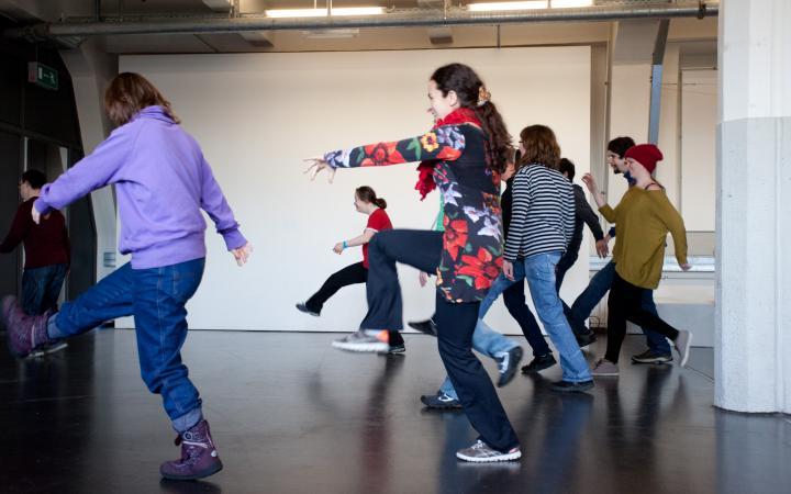 Eine Gruppe von Jugendlichen tanzt ausgelassen. Dabei werfen sie die Beine in die Höhe und lachen fröhlich.