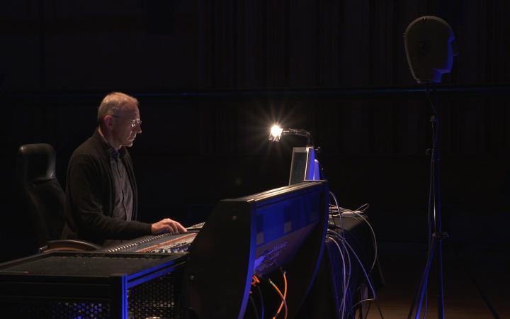 Auf dem Bild ist eine Person musizierend vor einem Mischpult zu sehen.