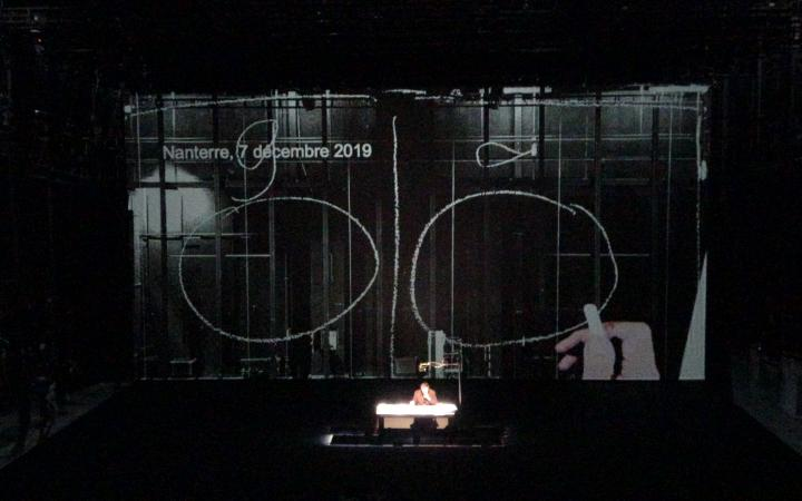 Bruno Latour is sitting on a stage behind a desk. Behind him is a large screen showing two large circles, with a long, vertical line between them.