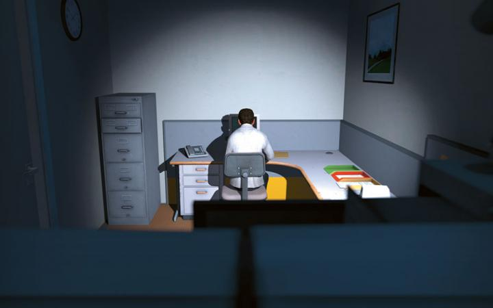 The view falls from behind on a man who is sitting at a desk in the dark