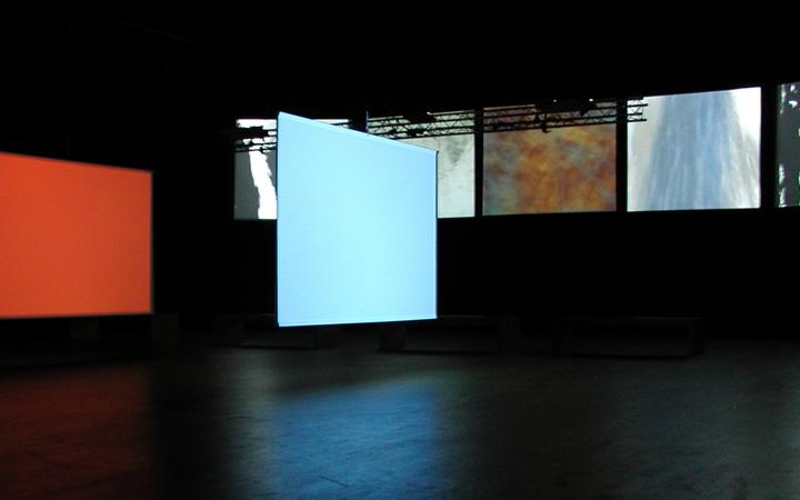 In einem dunklen Raum hängen sichtbar sieben Leinwände, auf die unterschiedliche abstrakte Bilder projiziert werden.