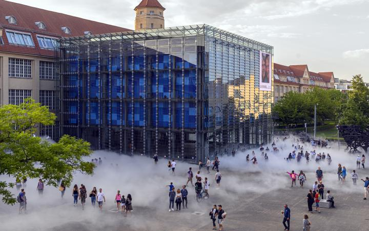 The photo was taken with a drone and shows the cube of the ZKM by day. A lot of people are gathered around the cube and are partly hidden behind the fog sculpture.