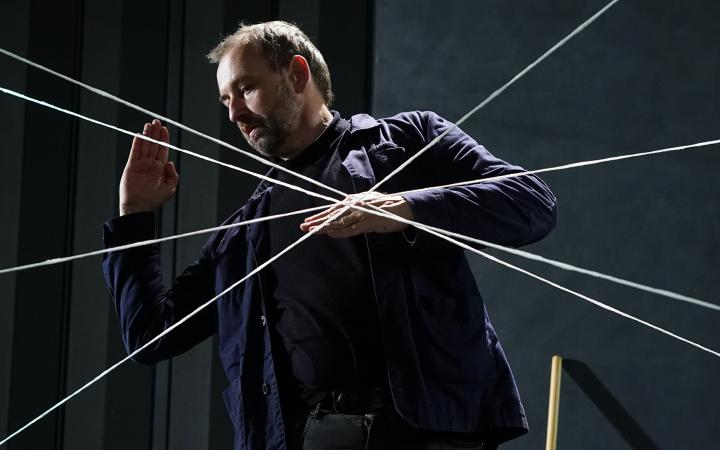 The picture shows a man performing with a strict body language in fron of a net of white rows.
