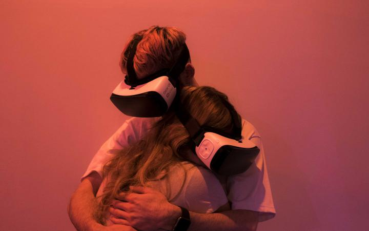 Two people with VR glasses hug each other