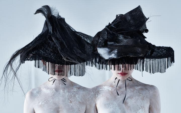 Portrait of two young women, who's eye areas are covered up with huge, triangular, black hats