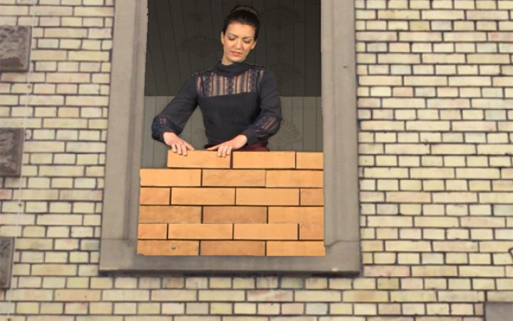 A woman stands at the window and walling herself in