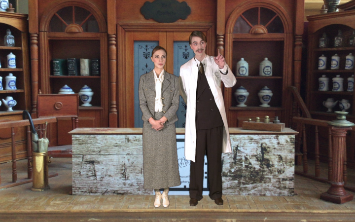 A woman and man are standing in front of shelves with glass vases