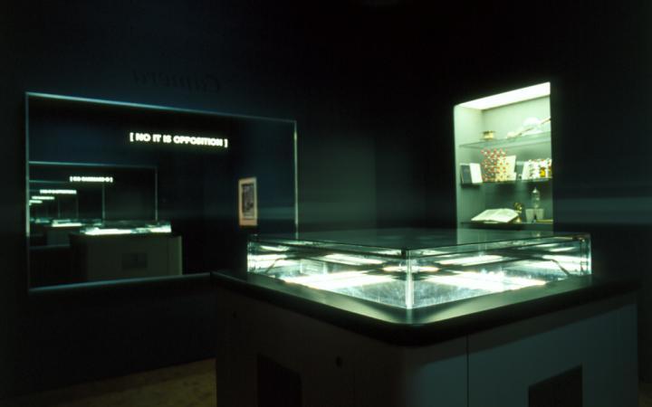 """Der Blick in die Ausstellung »Iconoclash« zeigt """"the typosophic pavilion""""  von Ecke Bonk  und Richard Hamilton: einen dunklen Raum mit erleuchteten Vitrinen und einem Spiegel mit der Aufschrift »No It Is Opposition«"""