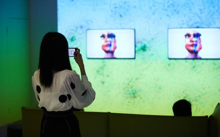 The photo shows the work »im here to learn so :)))))))«. In the background is a large screen on which a Google DeepDream is projected. Three screens in front of it show the head of the chatbot Tay.