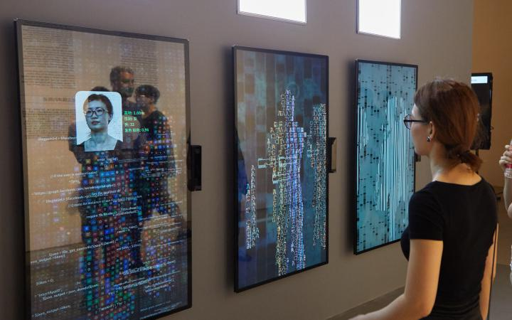 A woman stands in front of the artwork YOU:R:CODE that consists of large screens