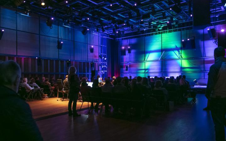 Ein abgedunkelter Raum mit sitzenden Menschen die auf eine Leinwand mit blauen und gelben Lichtstrahlen schauen.