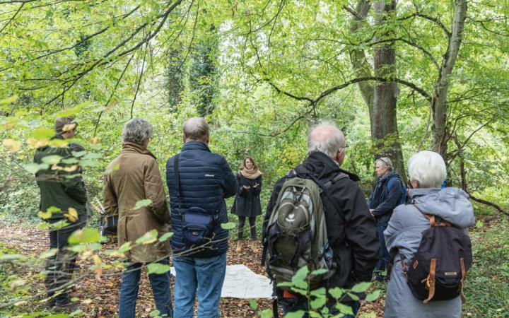 Eine Gruppe Menschen im Wald steht in Kreis um eine Frau, die spricht.