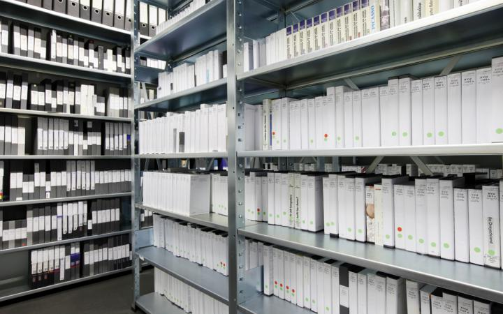 Shelves that are set full with video cassette shells and folders